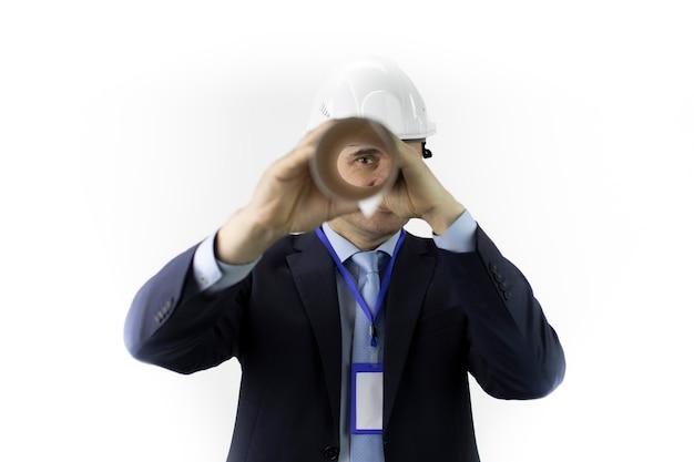 Ingegnere nel casco di sicurezza che guarda l'obbiettivo attraverso il modello attorcigliato in rotolo Foto Premium