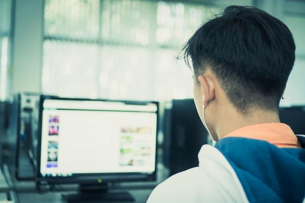 Ingegneri asiatici di male student di retrovisione che per mezzo del pc del computer per la ricerca di internet di dati di informazioni Foto Premium