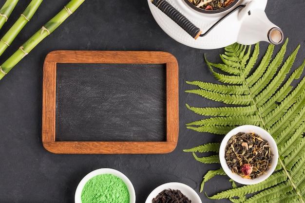 Ingrediente di tè sano con ardesia vuota e teiera su sfondo nero Foto Gratuite