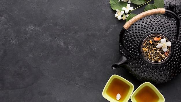 Ingrediente secco dell'erba del tè con la teiera nera sul fondo della pietra dell'ardesia Foto Gratuite