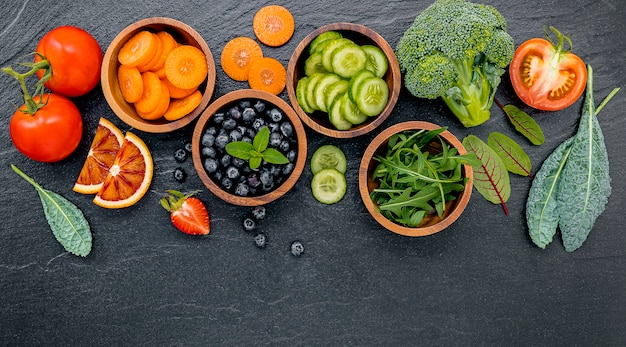 Ingredienti colorati per frullati e succhi sani su pietra scura Foto Premium