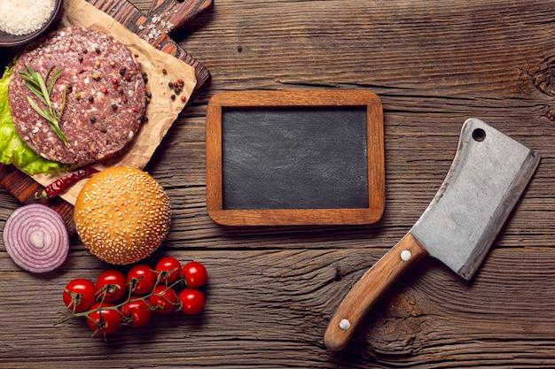 Ingredienti dell'hamburger di vista superiore con una lavagna Foto Gratuite