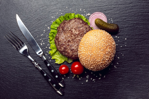 Ingredienti dell'hamburger di vista superiore su priorità bassa dell'ardesia Foto Gratuite