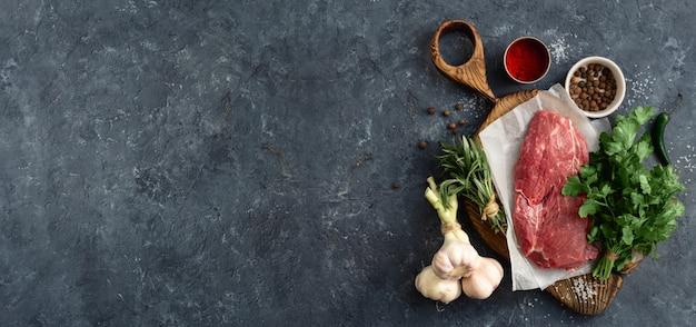 Ingredienti della carne cruda sul bordo di taglio di legno sulla pietra scura con la vista superiore del copyspace. menu del ristorante Foto Premium