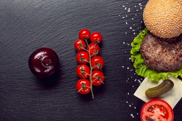 Ingredienti di hamburger piatto laici su sfondo di ardesia Foto Gratuite