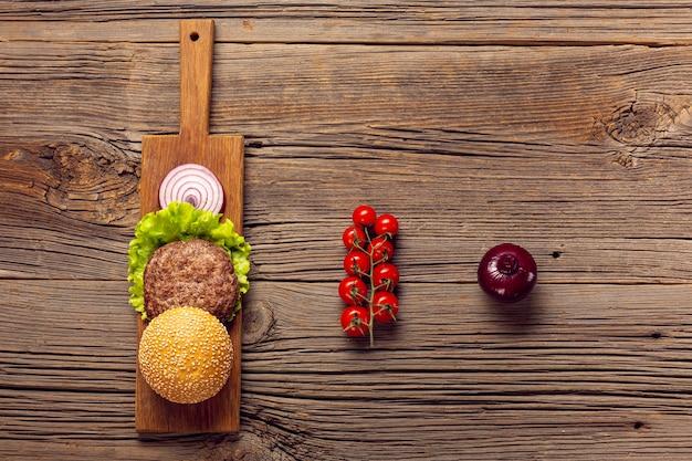 Ingredienti di hamburger piatto laici sul tavolo di legno Foto Gratuite