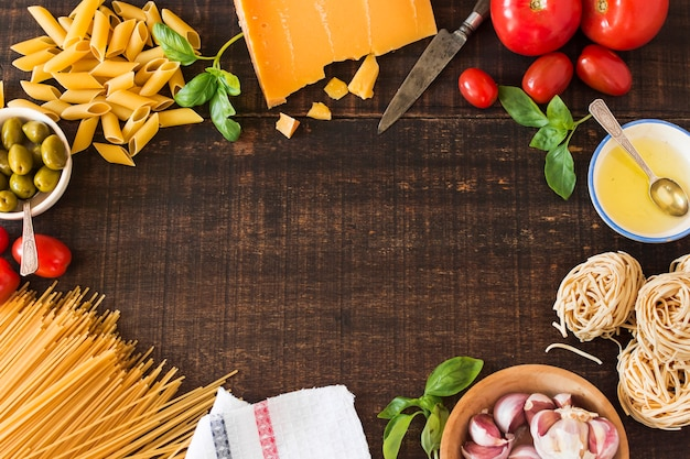 Ingredienti freschi per la cottura della pasta su fondo di legno Foto Gratuite