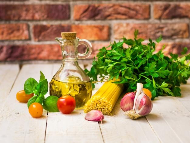Ingredienti pasto sano italiano, spaghetti, pomodori, olio d'oliva, aglio, basilico, erbe Foto Premium