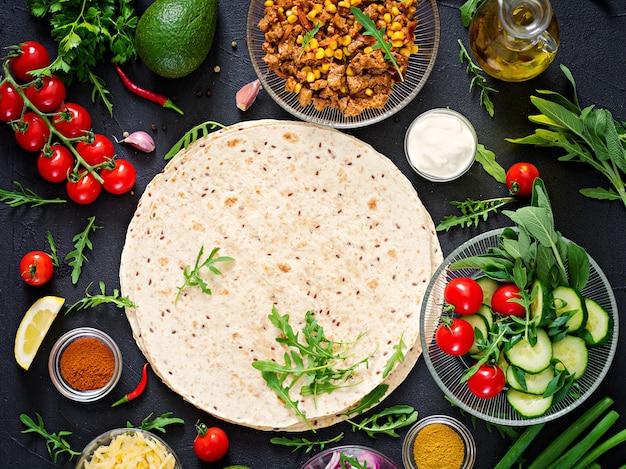 Ingredienti per burritos avvolge con carne e verdure su sfondo nero. vista dall'alto Foto Premium