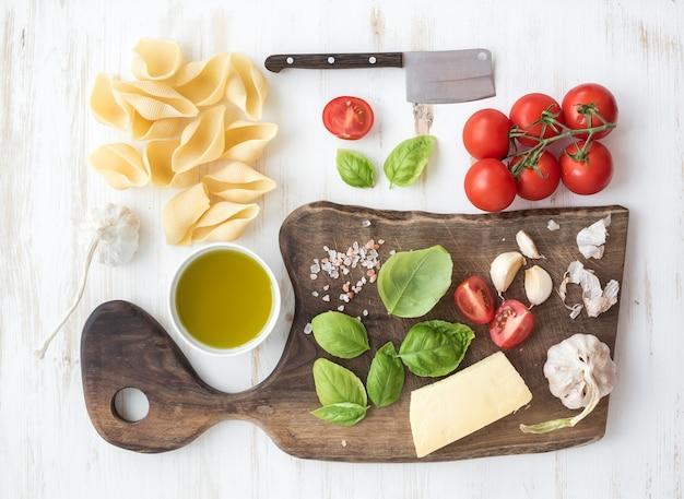 Ingredienti per cucinare la pasta. conchiglioni, foglie di basilico, pomodorini, parmigiano, olio d'oliva, sale, aglio su tagliere di noce rustico su legno bianco Foto Premium