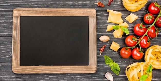 Ingredienti per il cibo italiano con lavagna accanto Foto Gratuite