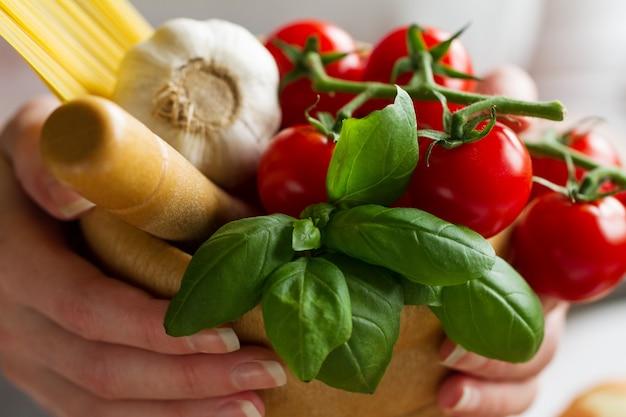 Ingredienti per la cottura della pasta. pomodori, basilico fresco, aglio, spaghetti. cook tiene ingredienti freschi per la cottura. avvicinamento. Foto Gratuite