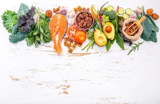 Ingredienti per la selezione di alimenti sani su fondo di legno bianco. Foto Premium