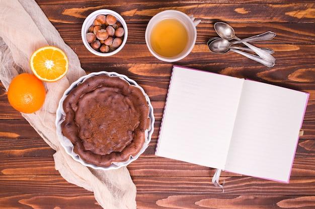 Ingredienti per torta al cioccolato con cucchiai e diario bianco sopra la scrivania in legno Foto Gratuite