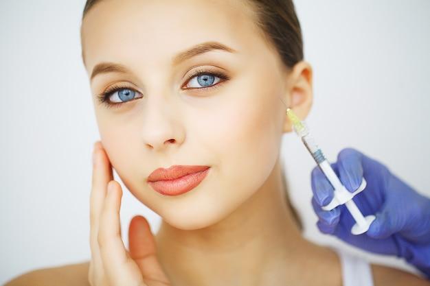 Iniezione di chirurgia plastica labbra sul viso di giovane donna Foto Premium