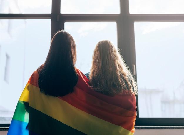 Innamorati lesbici avvolti nella bandiera lgbt Foto Gratuite
