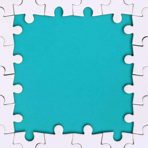 Inquadratura a forma di rettangolo, composta da un puzzle bianco attorno allo spazio blu Foto Premium