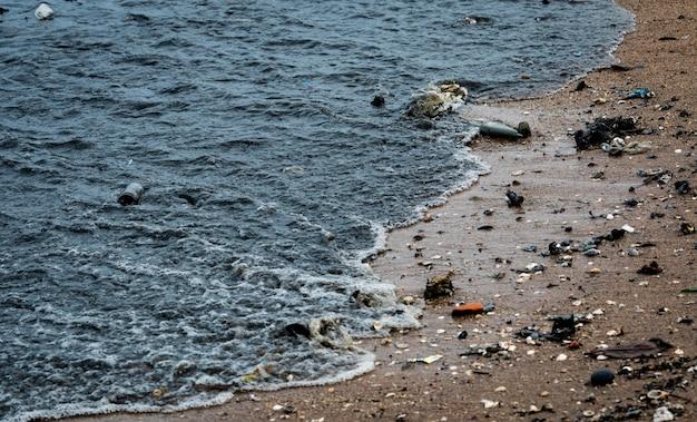 Inquinamento ambientale da spiaggia. macchie d'olio sulla spiaggia. perdita d'olio verso il mare. acqua sporca nell'oceano. inquinamento dell'acqua. nocivo per gli animali nell'oceano e nell'ambiente marino. acque reflue. Foto Premium