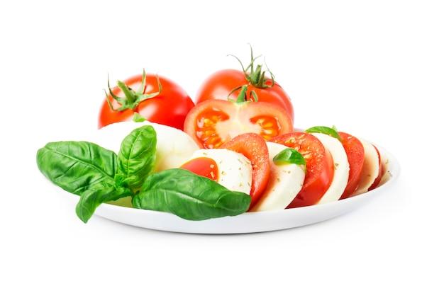 Insalata сaprese con pomodori maturi e mozzarella con foglie di basilico fresco. Foto Premium