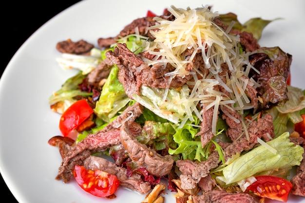 Insalata calda con carne e formaggio su un piatto bianco Foto Premium