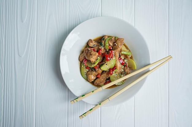Insalata calda con pollo, zucchine e peperoncino, semi di sesamo ed erbe aromatiche. Foto Premium