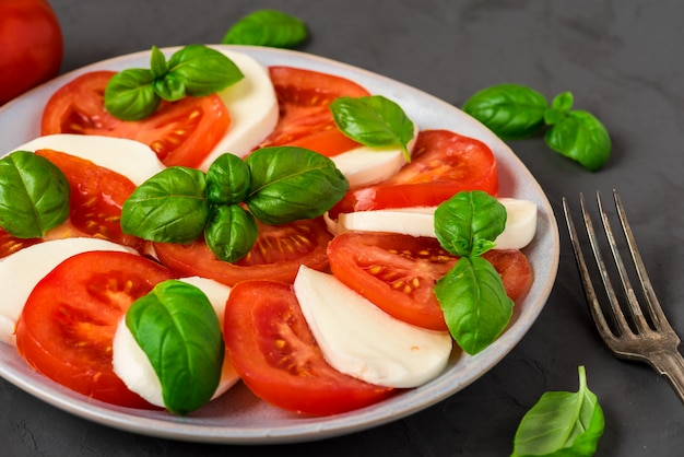 Insalata caprese con pomodori maturi e mozzarella, foglie di basilico fresco. cibo italiano Foto Premium