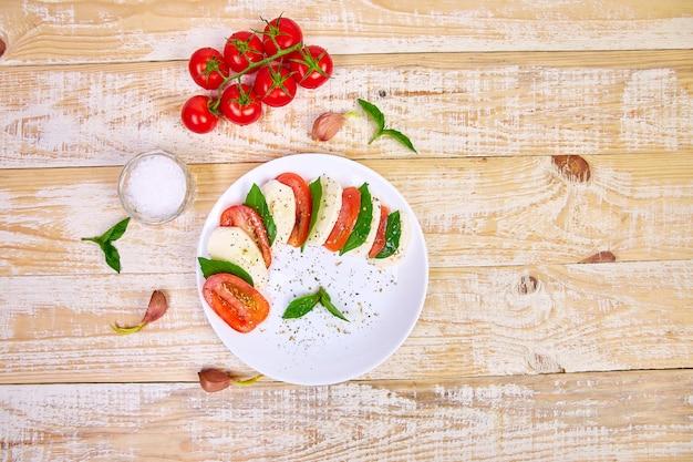 Insalata caprese italiana con fette di pomodoro, mozzarella, basilico, olio d'oliva. Foto Premium