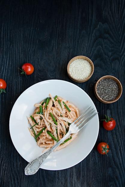 Insalata con ravanello daikon, cipolle verdi, miele e peperoncino rosso in polvere. insalata asiatica. disteso. . buio . Foto Premium