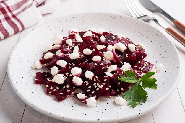 Insalata di barbabietola bollita e cagliata di grano con semi di sesamo su un piatto. Foto Premium
