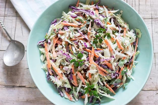 Insalata di cavoli di cavolo, carote e varie erbe con maionese in un grande piatto su un fondo di legno. Foto Premium