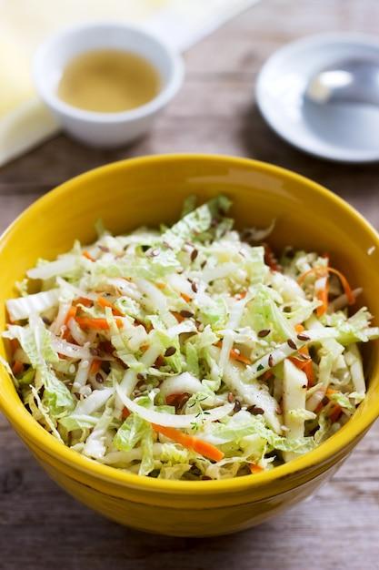 Insalata di cavoli di cavolo, carote e varie erbe con maionese in un grande piatto su una superficie di legno Foto Premium