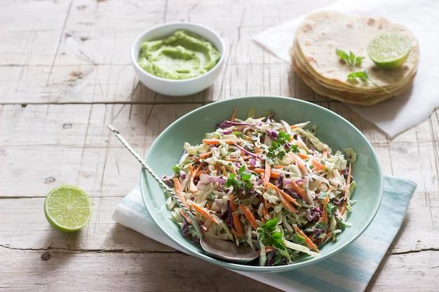 Insalata di cavolo a base di cavolo, carote ed erbe varie, servito con tortillas e guacamala su un fondo di legno. Foto Premium