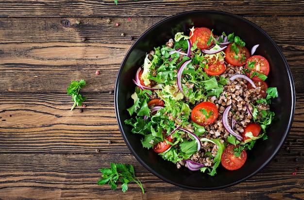 Insalata di grano saraceno con pomodorini, cipolla rossa ed erbe fresche. cibo vegano. menu dietetico. vista dall'alto. disteso Foto Gratuite