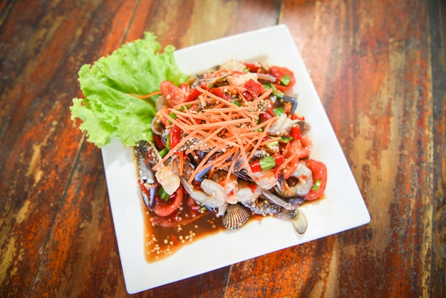 Insalata di mare speziata con gamberetti freschi granchi di granchio servita su piatto bianco verdure fresche erbe e spezie ingredienti con insalata di carote lattuga som tum menu tailandese asiatico Foto Premium