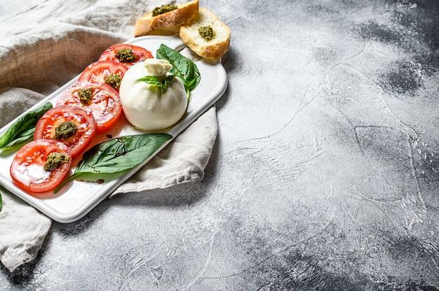 Insalata di mozzarella burrata con foglie di basilico e pomodori. sfondo grigio. vista dall'alto. spazio per il testo Foto Premium
