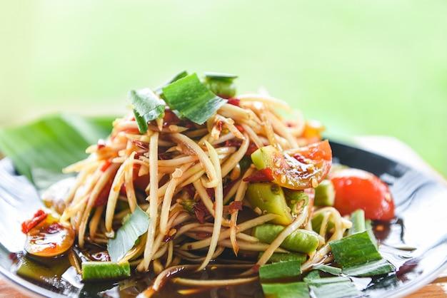 Insalata di papaia servita sul tavolo da pranzo insalata di papaya verde piccante cibo tailandese sul piatto con erbe e spezie ingredienti som tum menu tailandese cibo asiatico Foto Premium