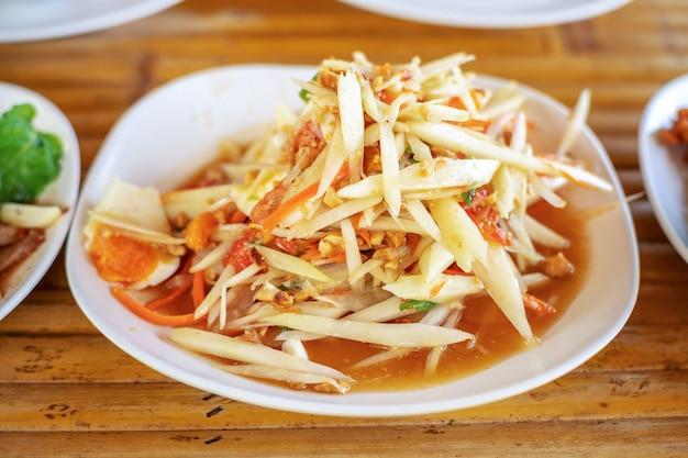 Insalata di papaya o som tam in cibo tailandese della via Foto Premium