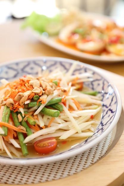 Insalata di papaya verde o som tam nel cibo tailandese di strada Foto Premium