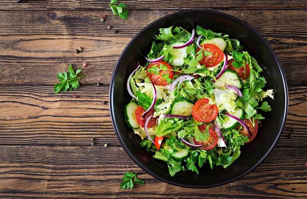 Insalata di pomodori, cetrioli, cipolle rosse e foglie di lattuga. menù vitaminico estivo salutare. alimenti vegetali vegani. tavolo da pranzo vegetariano. vista dall'alto. disteso Foto Gratuite
