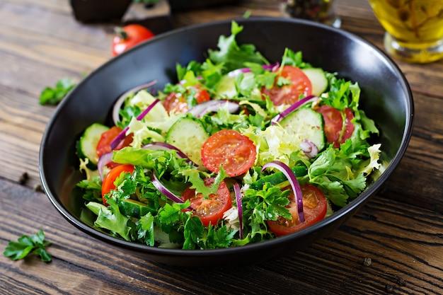 Insalata di pomodori, cetrioli, cipolle rosse e foglie di lattuga. menù vitaminico estivo salutare. alimenti vegetali vegani. tavolo da pranzo vegetariano. Foto Gratuite