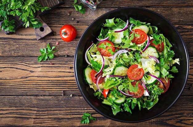 Insalata di pomodori, cetrioli, cipolle rosse e foglie di lattuga. Foto Premium