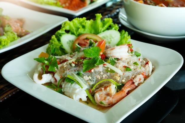 Insalata di spaghetti piccante, insalata di vermicelli piccanti con gamberetti freschi e calamari, stile cibo tailandese. Foto Premium