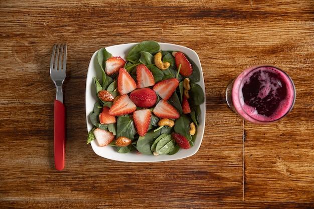 Insalata di spinaci e fragole con succo di barbabietola sul tavolo di legno Foto Premium
