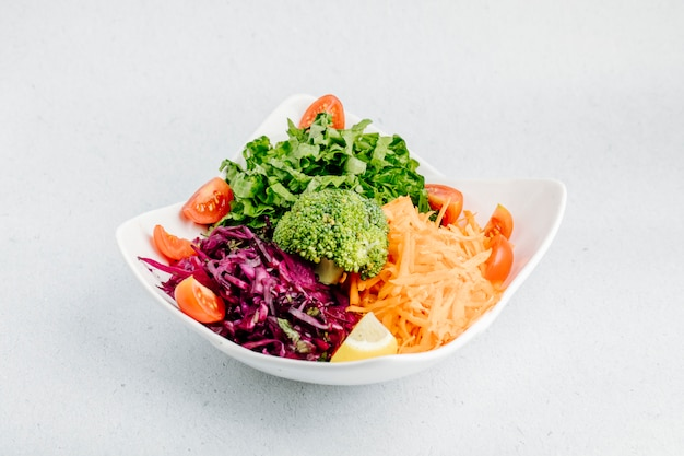 Insalata di verdure con cavolo tritato, carota, fette di pomodoro, lattuga e broccoli. Foto Gratuite