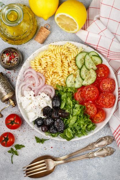 Insalata greca con pasta di fusilli, lattuga, pomodori, cetrioli, formaggio feta, cipolle rosse e olive nere Foto Premium
