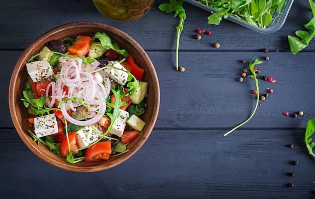 Insalata greca con pomodoro fresco, cetriolo, cipolla rossa, basilico, formaggio feta, olive nere e erbe italiane. vista dall'alto Foto Premium