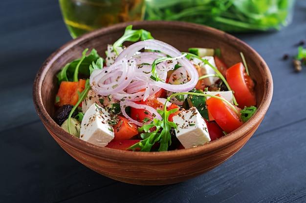 Insalata greca con pomodoro fresco, cetriolo, cipolla rossa, basilico, formaggio feta, olive nere e erbe italiane Foto Premium