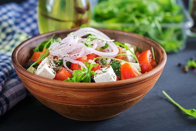 Insalata greca con pomodoro fresco, cetriolo, cipolla rossa, basilico, formaggio feta, olive nere ed erbe italiane Foto Gratuite
