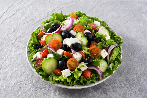 Insalata greca fresca nel piatto con olive nere, pomodoro, formaggio feta, cetriolo e cipolla su sfondo grigio Foto Premium