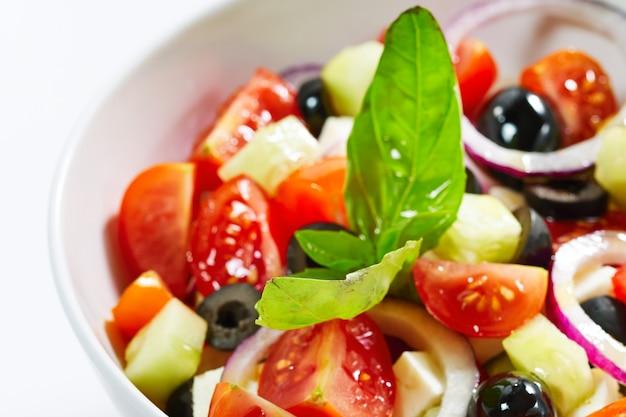 Insalata greca leggera con verdure fresche, guarnita con basilico. Foto Premium